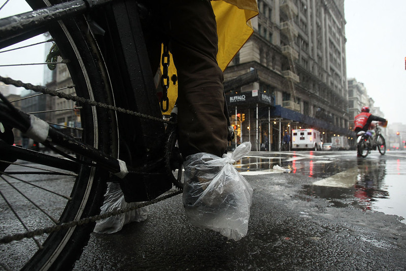 . NEW YORK, NY - FEBRUARY 08: A bicycle delivery man has his feet wrapped in plastic as he rides through wind, snow and sleet on Broadway as Manhattan prepares for a major winter storm on February 8, 2013 in New York City.  New York City and much of the Northeast is expected to get a foot or more of snow through Saturday afternoon with possible record-setting blizzard conditions expected. Heavy snow warnings are in effect from New Jersey through southern Maine.  (Photo by Spencer Platt/Getty Images)