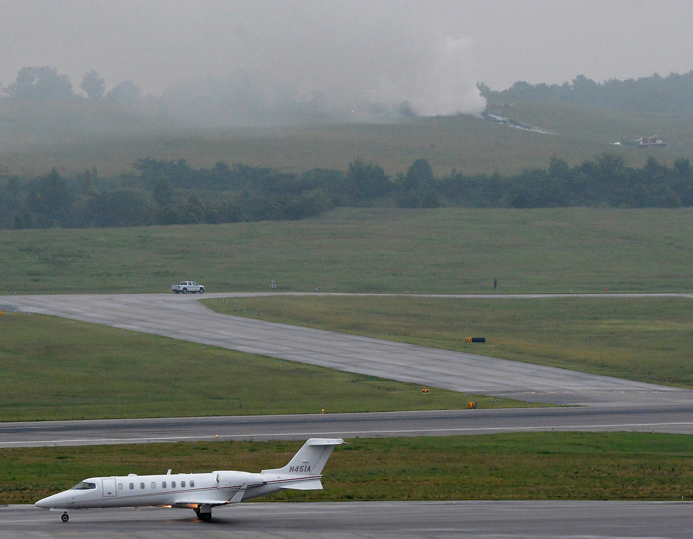 . A business jet taxis as smoke rises from a UPS cargo plane that crashed  on a hill at Birmingham-Shuttlesworth International Airport, Wednesday, Aug. 14,  2013, in Birmingham, Ala.  (AP Photo/ AL.com, Mark Almond)
