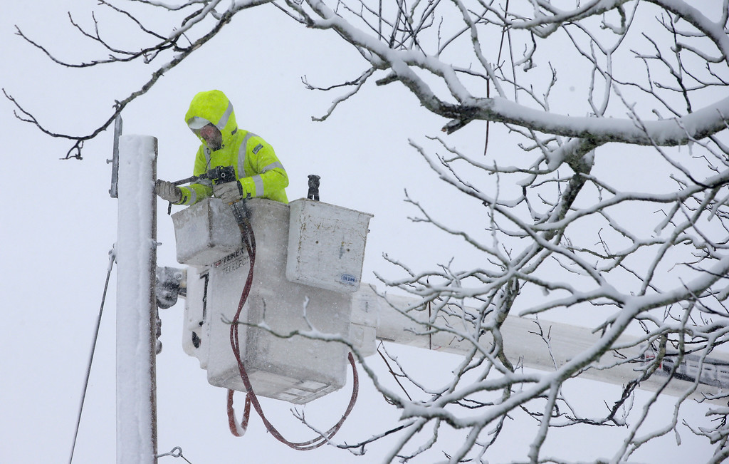 . A Worker repairs power lines during a winter storm, Tuesday, March 13, 2018, in Norwell, Mass.  A nor\'easter that could deliver up to 2 feet of snow to some areas socked New England on Tuesday, bringing blizzard conditions to parts of Massachusetts, covering highways with snow and knocking out power to tens of thousands. (AP Photo/Steven Senne)