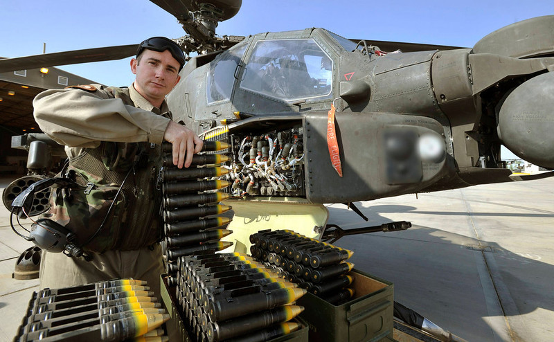 . Corporal Graham Carr, arming loading point commander (ALPC) of 662 Squadron, 3 Reg Army Air Corps, loads the Apache helicopter to be flown by Britain\'s Prince Harry, with rounds for the 30mm cannon, at Camp Bastion, southern Afghanistan in this photograph taken November 3, 2012, and released January 22, 2013.The Prince, who is serving as a pilot/gunner with 662 Squadron Army Air Corps, is on a posting to Afghanistan that runs from September 2012 to January 2013.  Photograph taken November 3, 2012. Photograph pixelated at source. REUTERS/John Stillwell/Pool