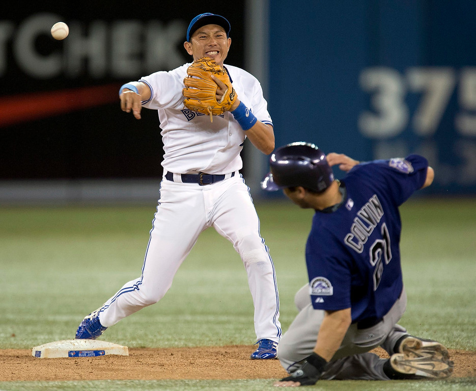 . Toronto Blue Jays Munenori Kawasaki,left, turns a double play on Colorado Rockies Tyler Colvin during a baseball game in Toronto on Monday June 17, 2013.  (AP Photo/The Canadian Press, Frank Gunn)