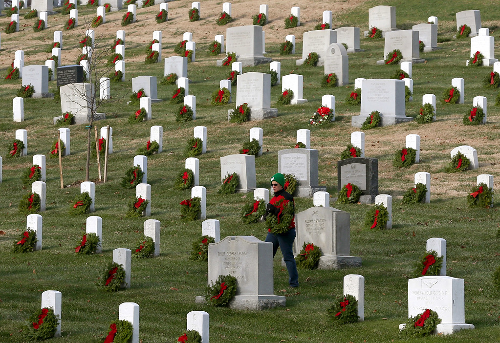 . A volunteer looks for a grave to place a wreath on during the National Wreaths Across America Day at Arlington National Cemetery, December 13, 2014 in Arlington, Virginia. Volunteers placed wreaths throughout the entire cemetery in honor of Arlington\'s 150th anniversary.  (Photo by Mark Wilson/Getty Images)