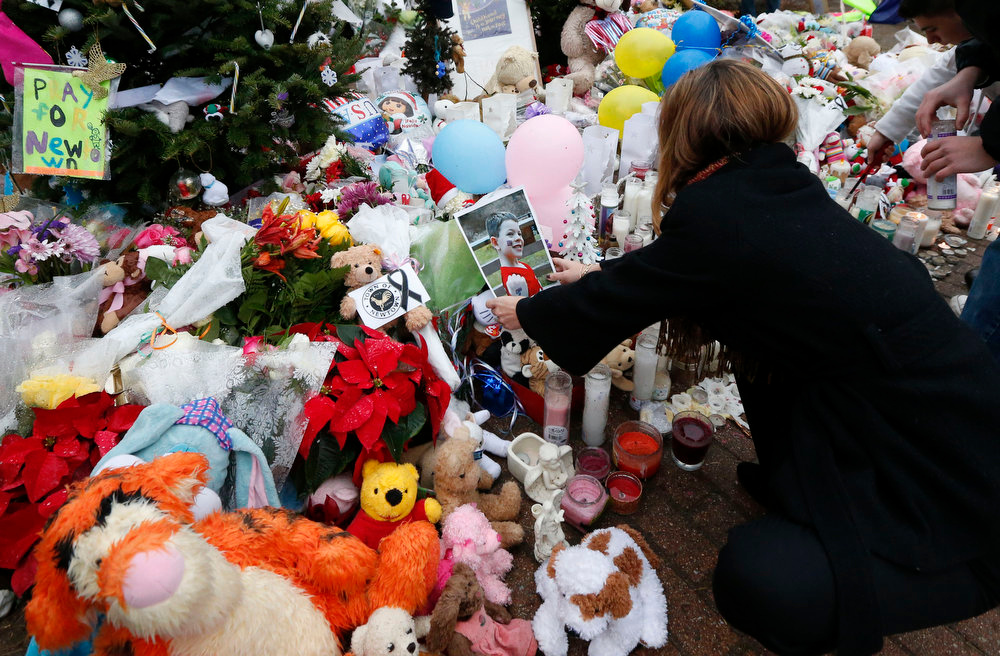 . A woman puts a photo of a child on a makeshift memorial in the Sandy Hook village of Newtown, Conn., as the town mourns victims killed in a school shooting, Monday, Dec. 17, 2012. (AP Photo/Julio Cortez)