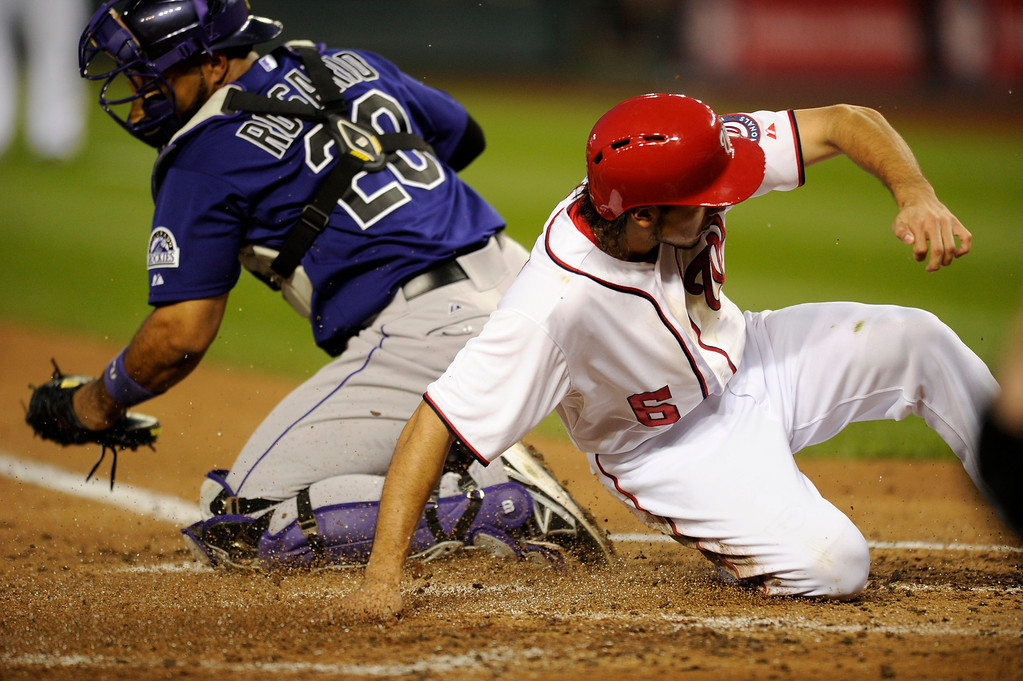 . Washington Nationals\' Anthony Rendon (6) slides home to score on a double by Ryan Zimmerman during the sixth inning of a baseball game against Colorado Rockies catcher Wilin Rosario (20), Friday, June 21, 2013, in Washington. The Nationals won 2-1. (AP Photo/Nick Wass)