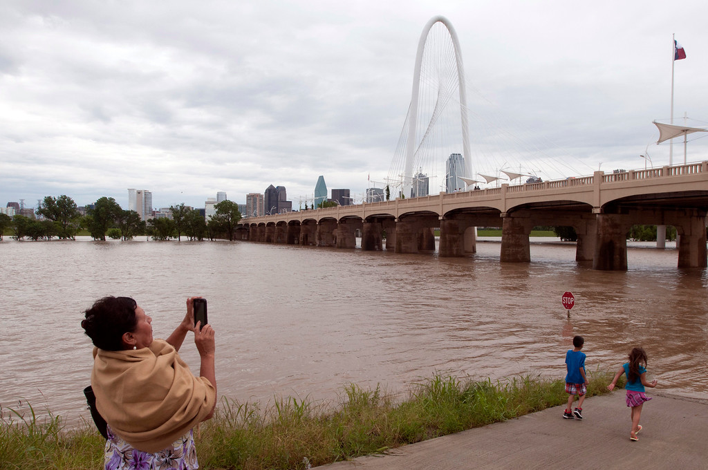 . Maria Sanchez takes photos on a closed path next to the Trinity River in Dallas on Saturday, May 30, 2015.  The National Weather Service has issued a flood watch for portions of Central and South Texas, which could see as much as five inches of rain Saturday if a storm system stalls over the area. (AP Photo/Rex C. Curry)