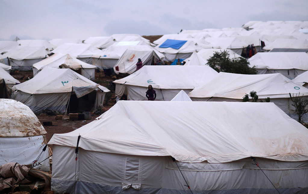 . In this Monday, Dec. 10, 2012 photo, Syrians who fled their homes stand by their tents at a camp for displaced Syrians, in the village of Atmeh, Syria. This tent camp sheltering some of the hundreds of thousands of Syrians uprooted by the country\'s brutal civil war has lost the race against winter: the ground under white tents is soaked in mud, rain water seeps into thin mattresses and volunteer doctors routinely run out of medicine for coughing, runny-nosed children. (AP Photo/Muhammed Muheisen)