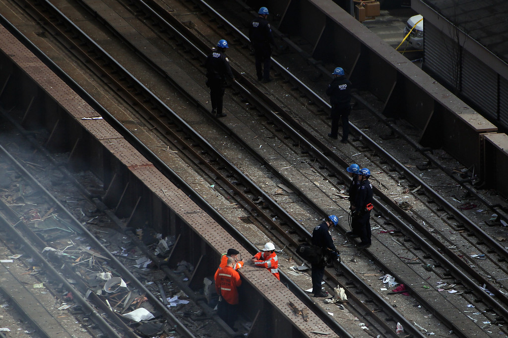 . Emergency personnel stand on the Metro-North train tracks as they respond to a five-alarm fire and building collapse at 1646 Park Ave in the Harlem neighborhood of Manhattan March 12, 2014 in New York City. (Photo by Justin Heiman/Getty Images)