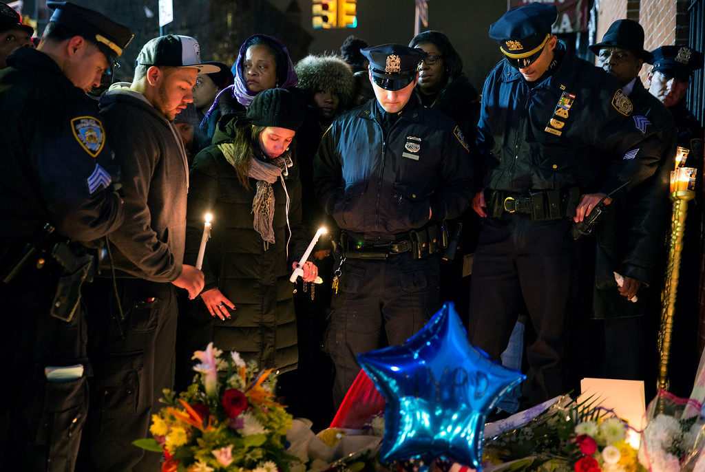 . Police officers and other mourners stand in silence, Sunday, Dec. 21, 2014, during a candlelight vigil near the spot where two New York Police Department officers, sitting inside a patrol car the previous day, were shot by an armed man, killing them both. The assailant then went into a nearby subway station and committed suicide, police said. (AP Photo/Craig Ruttle)
