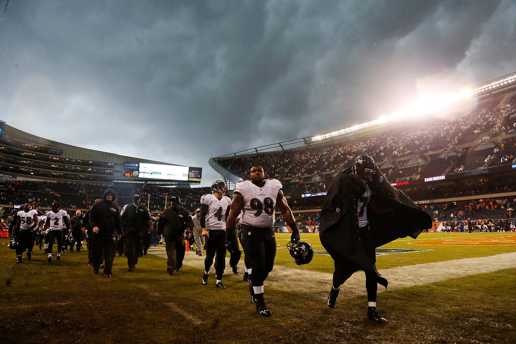 . Baltimore Ravens players leave the field as play was suspended for a severe thunderstorm blowing through Soldier Field during the first half of an NFL football game against the Chicago Bears, Sunday, Nov. 17, 2013, in Chicago. (AP Photo/Charles Rex Arbogast)