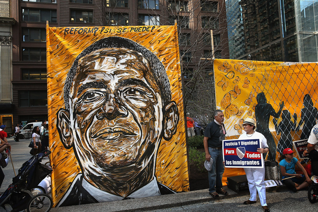 . CHICAGO, IL - MAY 01:  A portrait of President Barack Obama hangs in the Federal Building Plaza as demonstrators begin to gather following a May Day march on May 1, 2013 in Chicago, Illinois. Hundreds of protestors participated in the two-mile march from the city\'s West side into the Loop. The majority of the marchers were protesting for immigration reform.  (Photo by Scott Olson/Getty Images)