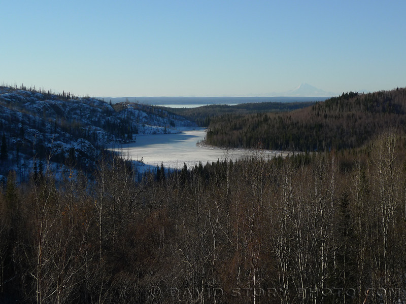 Shadows encroach across Upper Ohmer Lake with Skilak Lake and Redoubt behind.