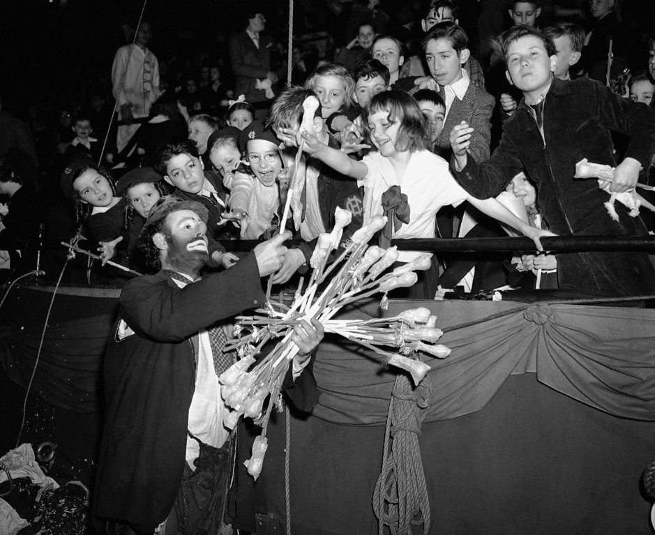 . Emmett Kelly, famous clown, hands out canes to impatient youngsters at the special circus show in Madison Square Garden in New York on May 10, 1943 for crippled, orphaned, and underprivileged children. (AP Photo)
