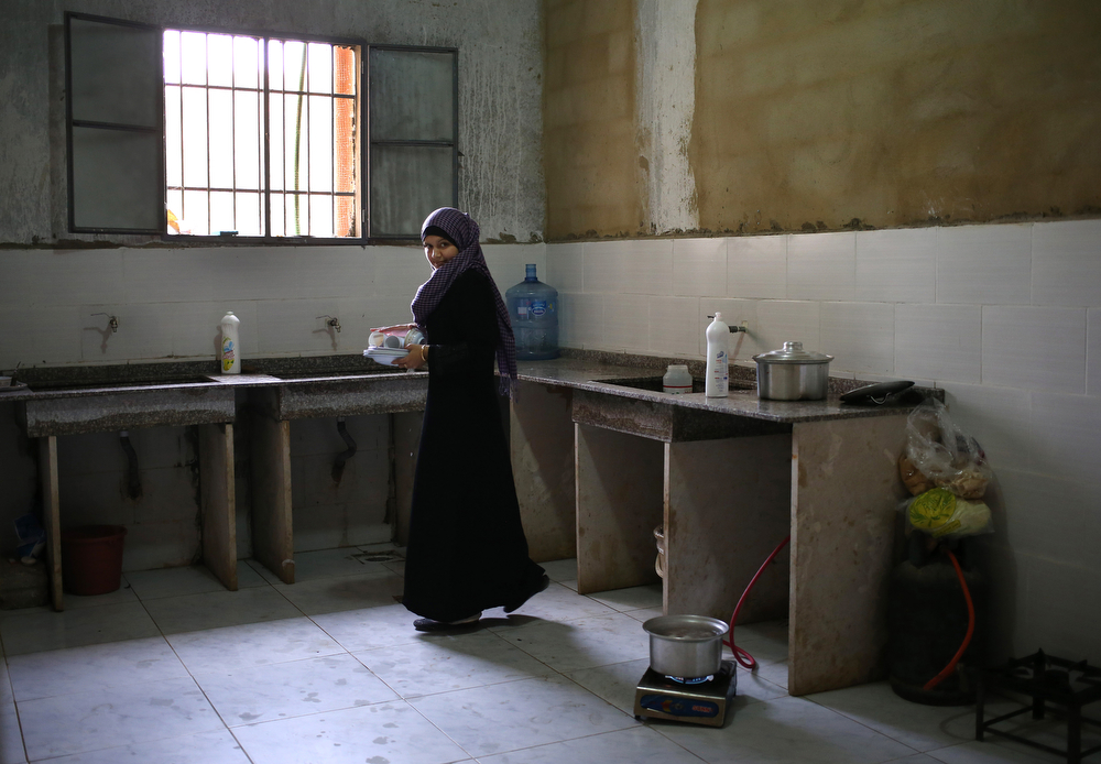 . In this picture taken on Thursday, May 29, 2014, a Syrian refugee woman carries plates after she washed them in a shared kitchen in a collective center where many Syrian refugees live, in Kirbet Daoud village in Akkar, north Lebanon. (AP Photo/Hussein Malla)