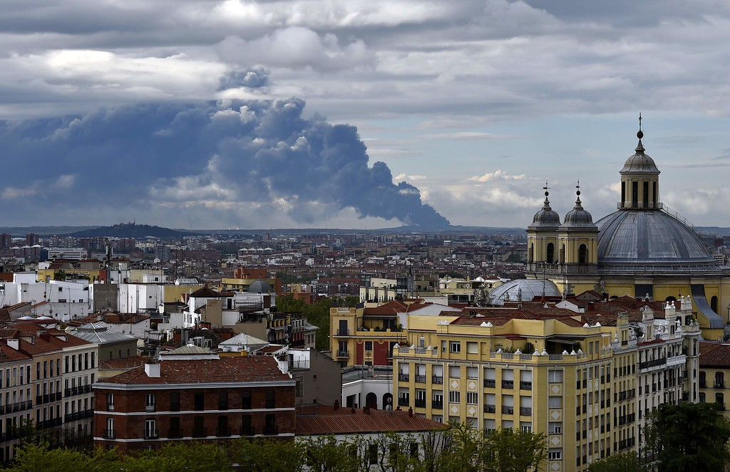 . Picture taken from the Almudena cathedral in Madrid shows a huge smoke column caused by a fire in an uncontrolled dump near the town of Sesena, on May 13, 2016. A huge waste ground near Madrid where millions of tires have been dumped was on fire today, releasing a thick black cloud of toxic fumes that officials worry could harm residents nearby.   / AFP PHOTO / GERARD JULIEN/AFP/Getty Images