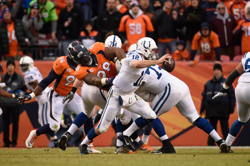 . Andrew Luck (12) of the Indianapolis Colts scrambles while under pressure from Terrance Knighton (98) of the Denver Broncos in the second quarter. The Denver Broncos played the Indianapolis Colts in an AFC divisional playoff game at Sports Authority Field at Mile High in Denver on January 11, 2015. (Photo by AAron Ontiveroz/The Denver Post)