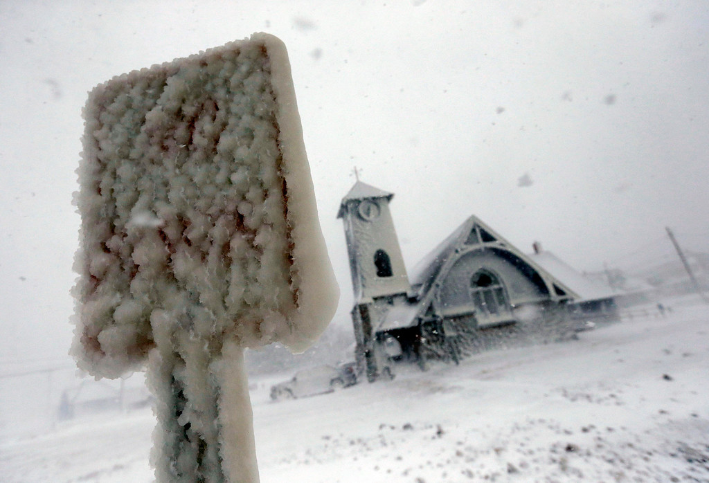 . Frozen sea spray coats a road sign and a church during a winter storm in Marshfield, Mass., Tuesday, Jan. 27, 2015. The storm punched out a section of the seawall in the coastal town, police said. (AP Photo/Michael Dwyer)