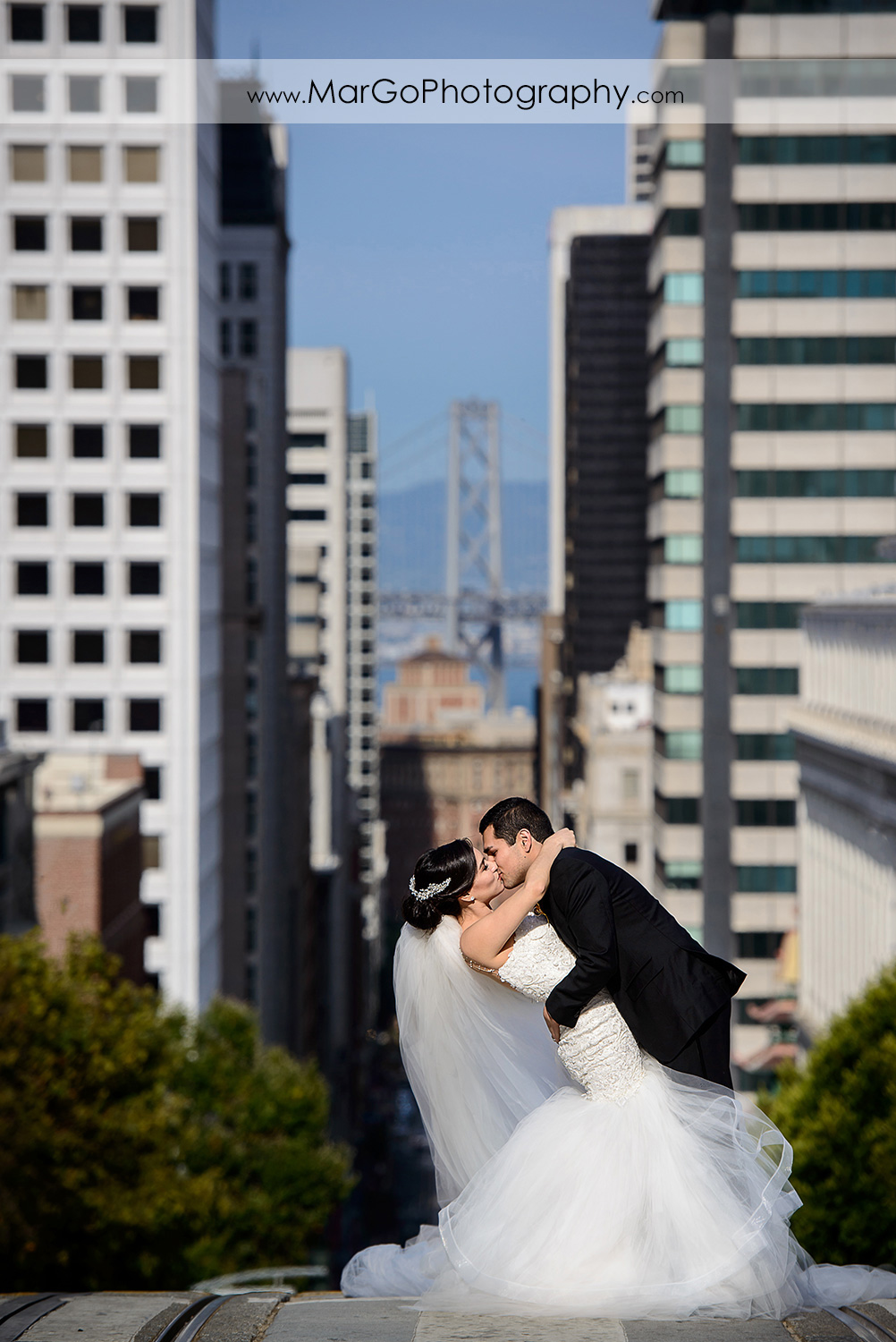 bride and groom kissing on the street of San Francisco with Bay Bridge in the background