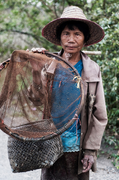 Local woman from a small hamlet returning home with her daily catch of small fish.  Northern Thailand, 2010.