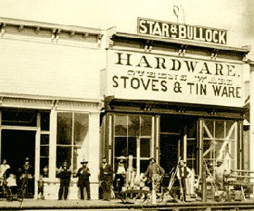 "One of the earlier business ventures undertaken by Bullock and Star was a hardware store in downtown Deadwood.  Perhaps reflecting who had the money in this partnership, notice that the building sign lists Star's name first.  Professor Wolff's research determined that Star was the ""majority partner.""    By the early 1880s, Star and Bullock had stores in Billings, Miles, City, Sundance, Sturgis,and Carbonate — and then Spearfish.  Bullock had tired of the business and was out of it by 1900."