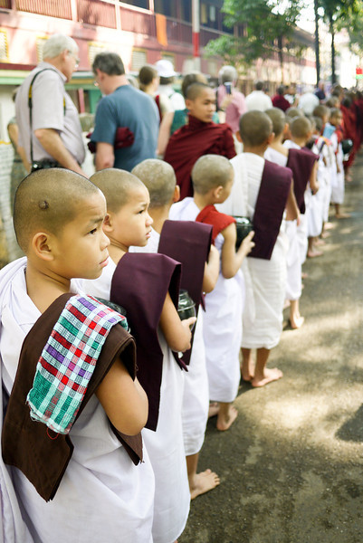 Young monks line up in rows and prepare for lunch at 11am at the Maha Gandayon Monastery in Mandalay, Burma.