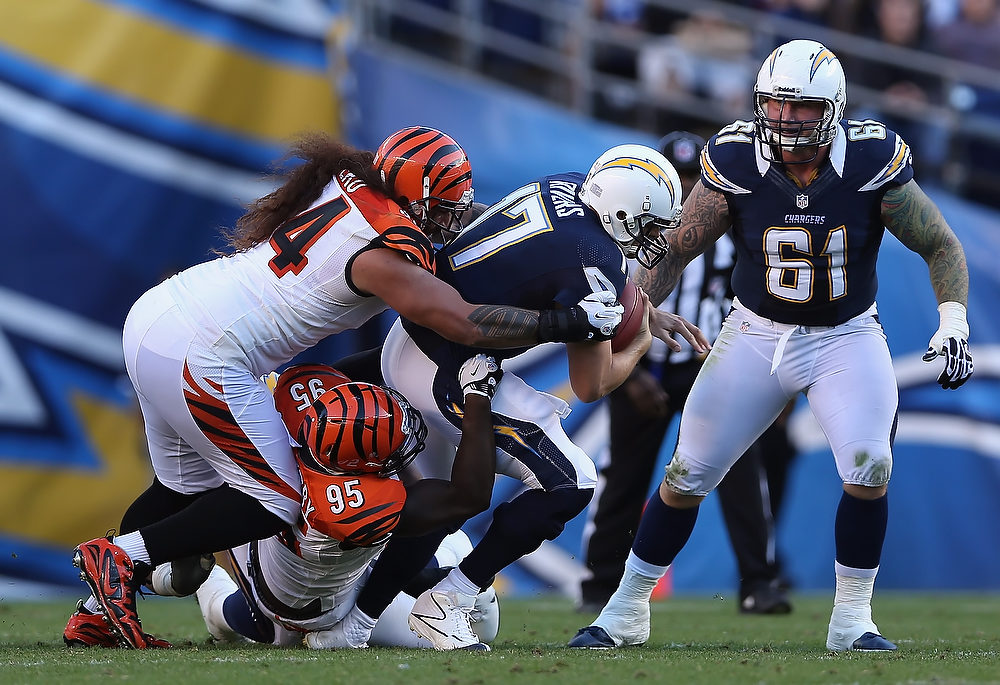 . Quarterback Philip Rivers #17 of the San Diego Chargers is brought down by Wallace Gilberry #95 and Domata Peko #94 of the Cincinnati Bengals, as Nick Hardwick #61 of the Chargers looks on in the second half at Qualcomm Stadium on December 2, 2012 in San Diego, California. The Bengals defeated the Chargers 20-13.  (Photo by Jeff Gross/Getty Images)