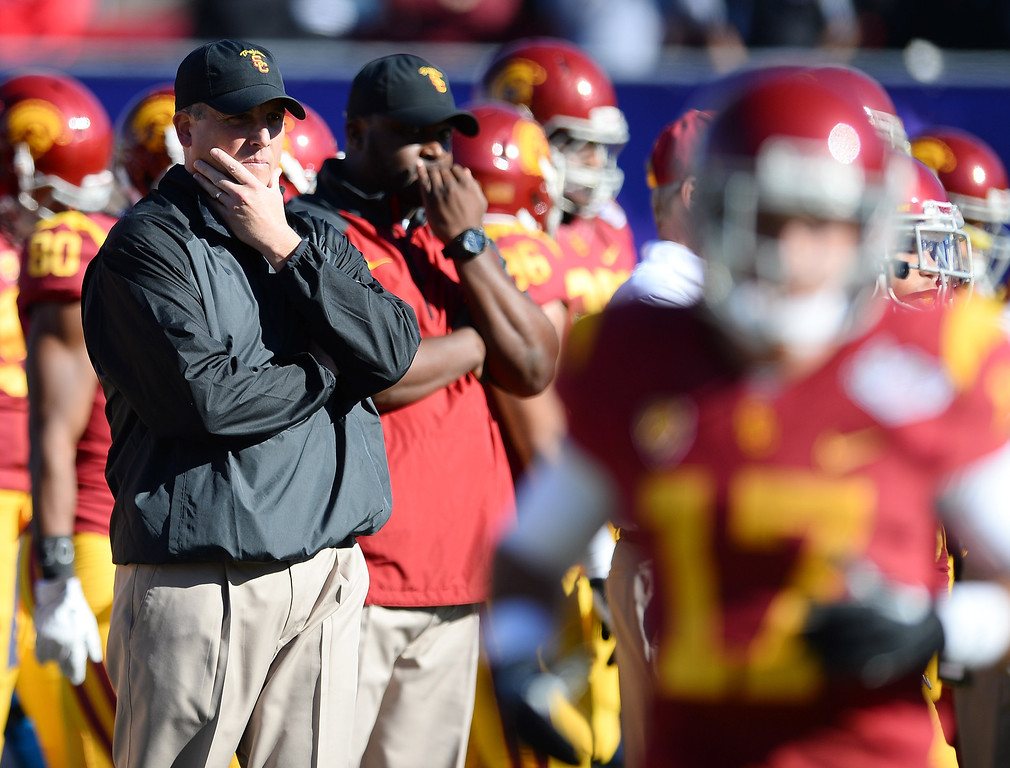 . LAS VEGAS, NV - DECEMBER 21:  USC Trojans interim coach Clay Helton (L) watches his team warm up before playing the Fresno State Bulldogs in the Royal Purple Las Vegas Bowl at Sam Boyd Stadium on December 21, 2013 in Las Vegas, Nevada. USC won 45-20.  (Photo by Ethan Miller/Getty Images)