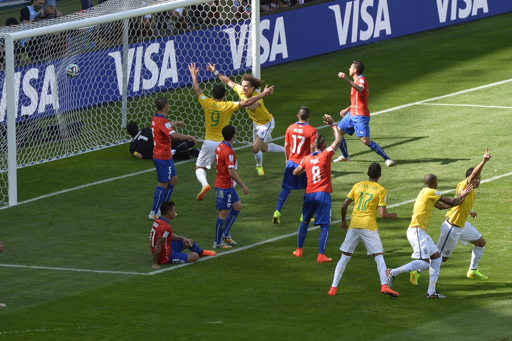 . Brazil\'s players celebrate as Chile\'s goalkeeper Claudio Bravo (L) concedes a goal during the round of 16 football match between Brazil and Chile at The Mineirao Stadium in Belo Horizonte during the 2014 FIFA World Cup on June 28, 2014.  (ODD ANDERSEN/AFP/Getty Images)