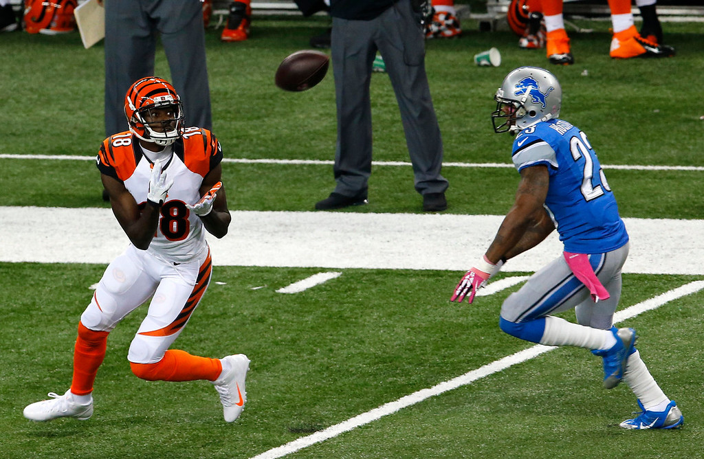 . Cincinnati Bengals wide receiver A.J. Green (18) makes an 82-yard touchdown reception as Detroit Lions cornerback Chris Houston (23) defends in the first quarter of an NFL football game Sunday, Oct. 20, 2013, in Detroit. (AP Photo/Paul Sancya)