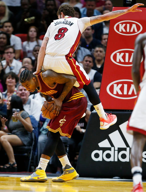 . Miami Heat guard Tyler Johnson (8) lands on Cleveland Cavaliers guard Iman Shumpert after trying to prevent a shot during the second half of an NBA basketball game, Monday, April 10, 2017, in Miami. The Heat defeated the Cavaliers 124-121 in overtime. (AP Photo/Wilfredo Lee)