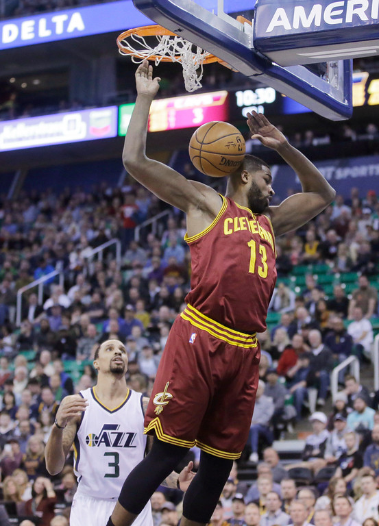 . Cleveland Cavaliers center Tristan Thompson (13) dunks the ball as Utah Jazz guard George Hill (3) looks on in the first half during an NBA basketball game Tuesday, Jan. 10, 2017, in Salt Lake City. (AP Photo/Rick Bowmer)