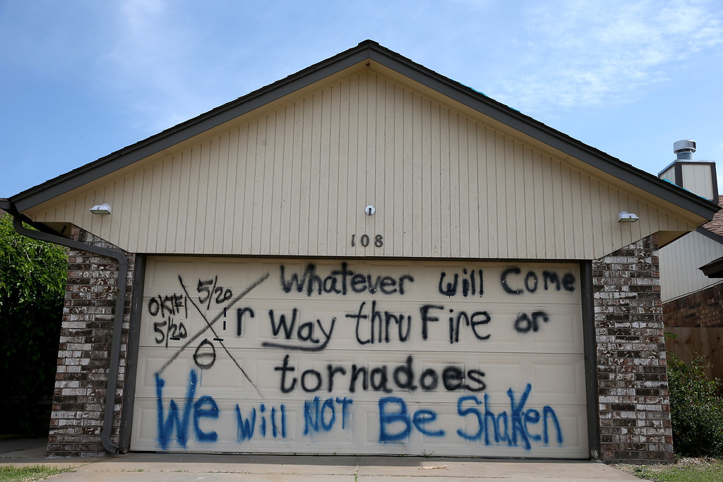 """. A sign reading \""""Whatever will come or way thru fire or tornadoes we will not be shaken\"""" is seen painted on the garage door of a home as the town prepares for Tuesday\'s one year anniversary of the town being devastated by a tornado on May 18, 2014 in Moore, Oklahoma.  On May 20, 2013, a two-mile wide EF5 tornado touched down in the town, killing 24 people and leaving behind extensive damage to homes and businesses.  (Photo by Joe Raedle/Getty Images)"""