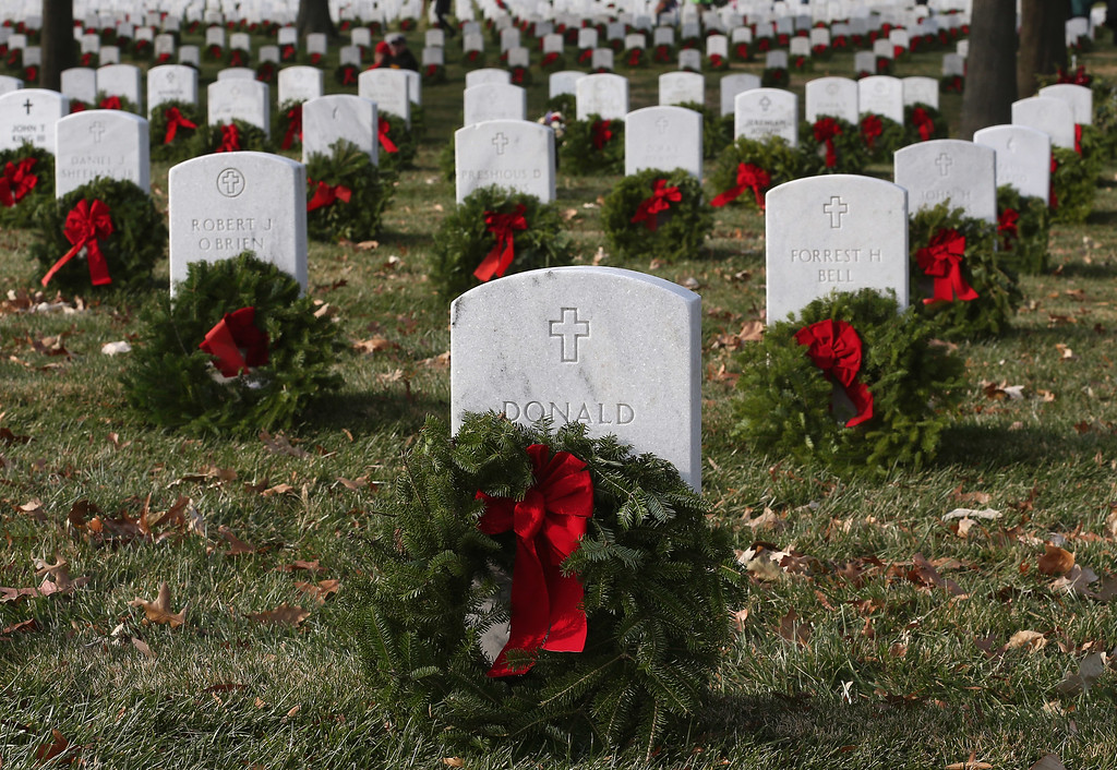 . Wreaths are placed on graves during the National Wreaths Across America Day at Arlington National Cemetery, December 13, 2014 in Arlington, Virginia. Volunteers placed wreaths throughout the entire cemetery in honor of Arlington\'s 150th anniversary.  (Photo by Mark Wilson/Getty Images)