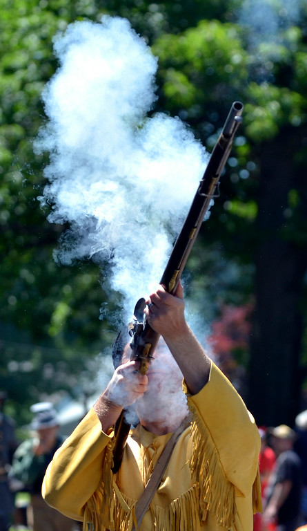 . Jeff Forman/JForman@News-Herald.com Ramrod Buster Justin Hanson fires his musket as he marches in the Mentor Headlands July 4th Parade.