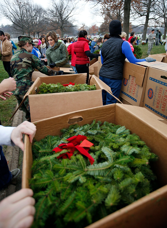 . Wreaths are unboxed as volunteers come to get them to place them at graves during Wreaths Across America at Arlington National Cemetery, Saturday, Dec. 12, 2015 in Arlington, Va. Organizers estimated that volunteers placed 240,815 wreaths at Arlington. (AP Photo/Alex Brandon)