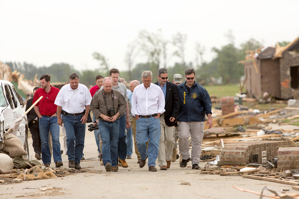 . Arkansas Gov. Mike Beebe, third from right, surveys the tornado damage along Aspen Creek Drive in the Parkwood neighborhood off Naylor Road in Vilonia, Ark. after a tornado struck the town. Vilonia was hit hard Sunday after a tornado system ripped through several states in the central U.S. and left more than a dozen dead in a violent start to this year\'s storm season, officials said. (AP Photo/Karen E. Segrave)