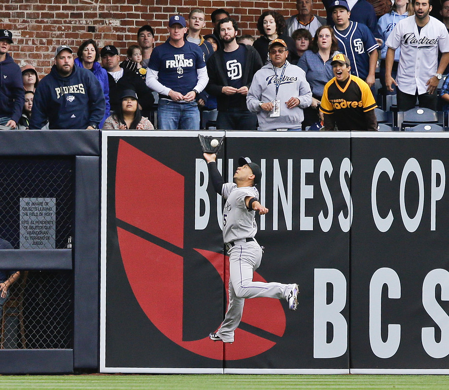 . Colorado Rockies left fielder Carlos Gonzalez robs San Diego Padres\' Yonder Alonso of an extra base hit during the first inning of a baseball game on Saturday April 13, 2013, in San Diego. The sacrifice fly did bring in a run for the Padres. (AP photo/Lenny Ignelzi)
