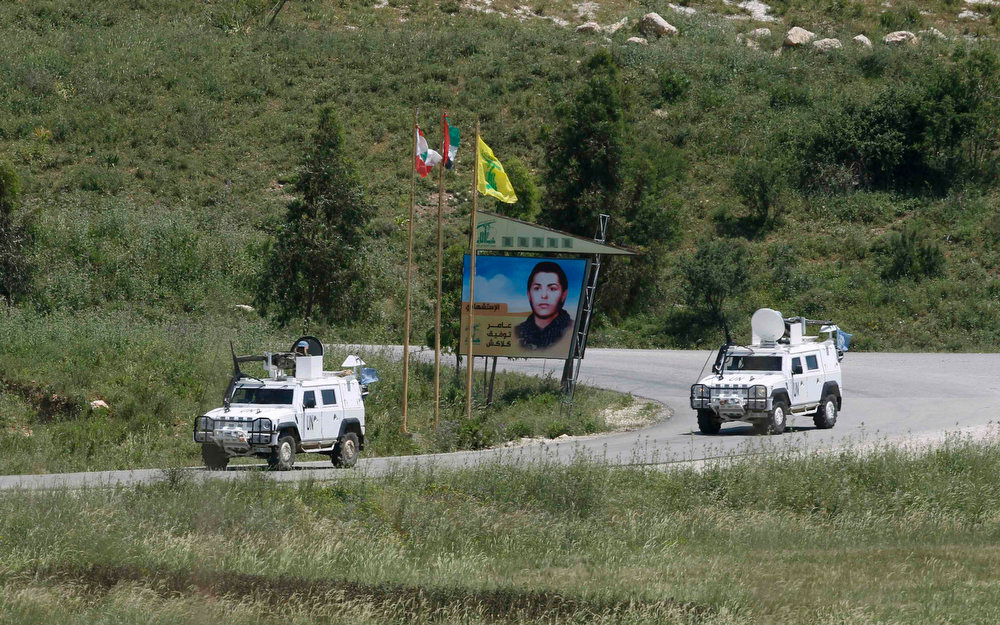 . U.N. peacekeepers drive past Lebanese, Palestinian and Hezbollah flags on the Lebanese side of the Israel-Lebanon border near the northern Israeli town of Metula May 5, 2013. U.N. Secretary-General Ban Ki-moon on Sunday voiced alarm at reports Israel has struck targets inside Syria, but said the United Nations was unable to confirm whether any such attacks had taken place. REUTERS/Baz Ratner