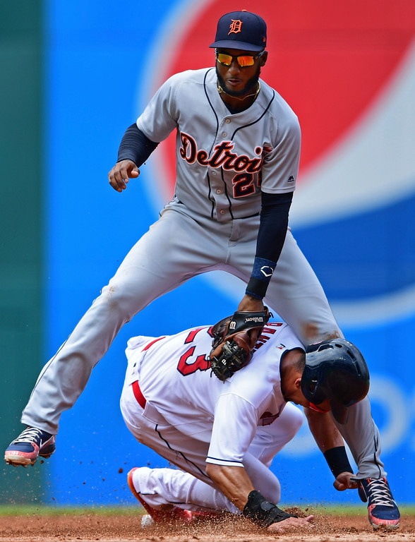 . Cleveland Indians\' Michael Brantley, bottom, steals second as Detroit Tigers\' Niko Goodrum is late on the tag in the second inning of a baseball game, Sunday, June 24, 2018, in Cleveland. (AP Photo/David Dermer)