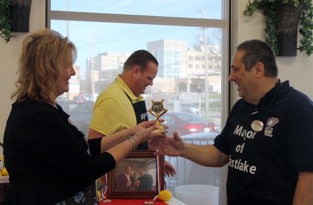 . Kristi Garabrandt � The News-Herald <br> Chick Fil-A Willoughby owner, Billie Federer, awards the trophy to Eastlake Mayor Dennis Morley after he was declared winner of the lemon squeeze competition.