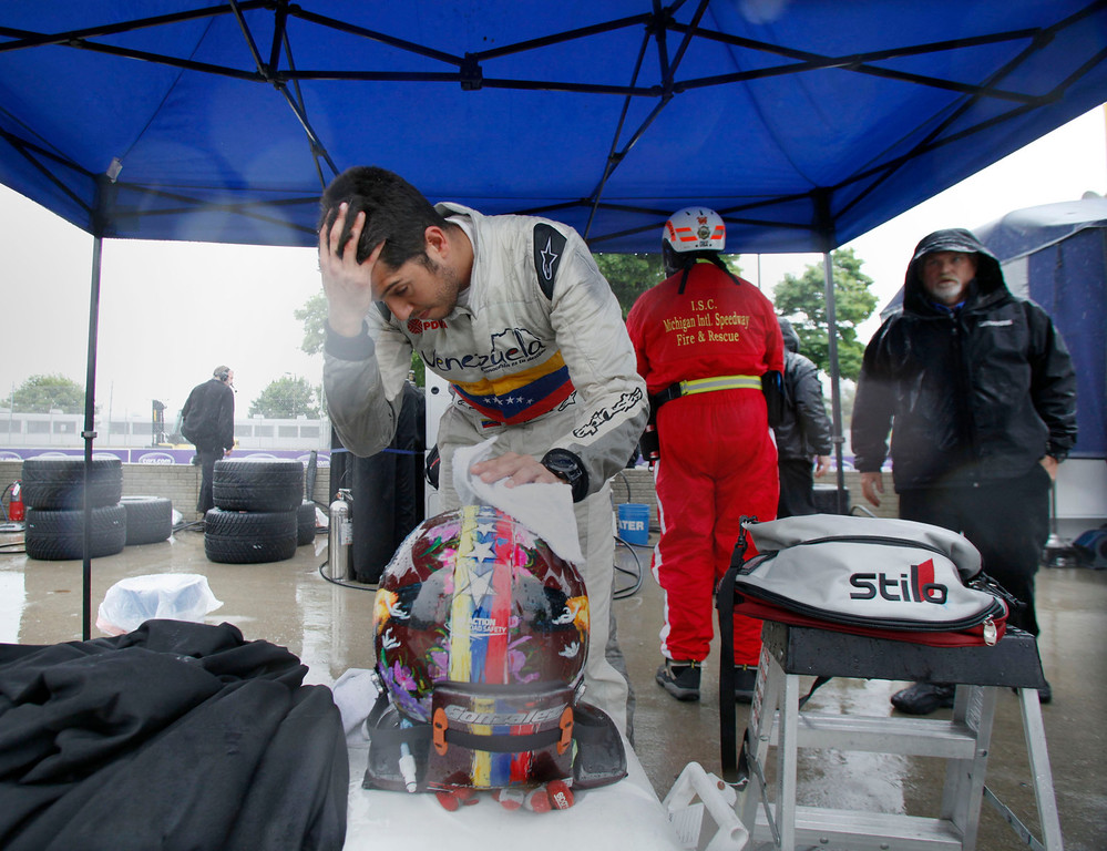 . Rodolfo Gonzalez dries off his helmet after taking some practice laps in the rain before the IndyCar Detroit Grand Prix auto race Sunday, May 31, 2015. (Diane Weiss/Detroit Free Press via AP)