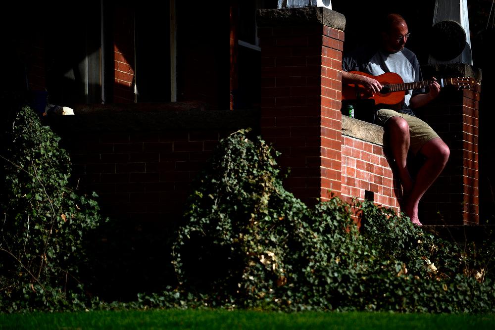 . Jeff Cowan strums his guitar near Washington Park. Temperatures reached the low 80s in Denver. (Photo by AAron Ontiveroz/The Denver Post)