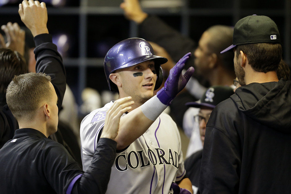 . MILWAUKEE, WI - APRIL 2: Troy Tulowitzki #2 of the Colorado Rockies celebrates in the dugout after scoring Dexter Fowler in the top of the seventh inning on a sacrafice fly against the Milwaukee Brewers at Miller Park on April 2, 2013 in Milwaukee, Wisconsin. (Photo by Mike McGinnis/Getty Images)