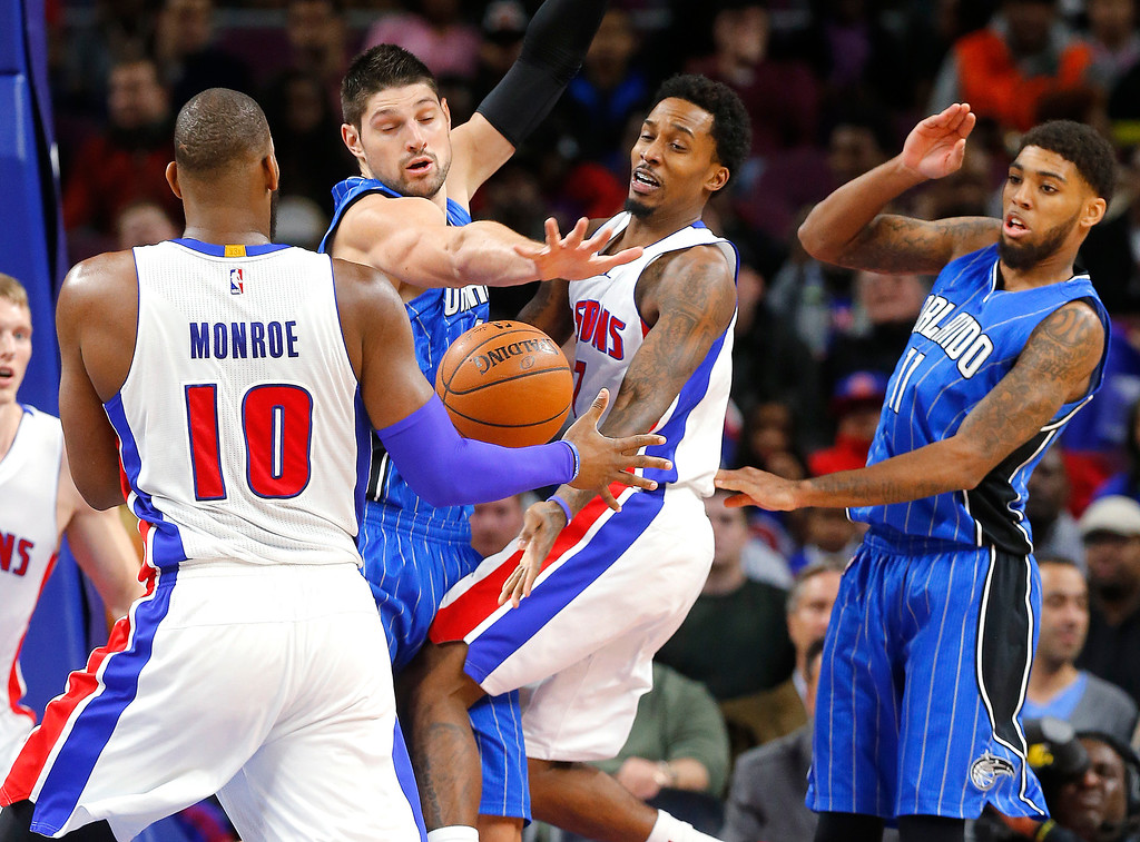 . Detroit Pistons guard Brandon Jennings (7) passes to Greg Monroe (10) as Orlando Magic center Nikola Vucevic, third from right, defends and Pistons\' Devyn Marble (11) looks on in the first half of an NBA basketball game in Auburn Hills, Mich., Wednesday, Jan. 21, 2015. (AP Photo/Paul Sancya)