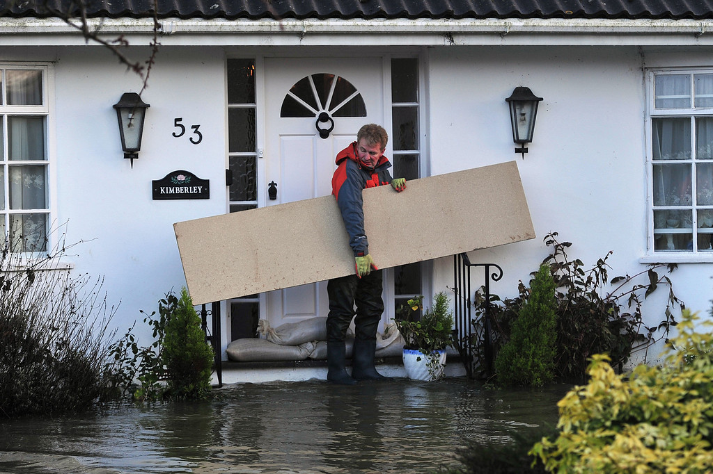 . A resident tries to construct flood defenses in the village of Wraysbury, west of London on February 12, 2014.  Flooded communities in Britain faced a fresh battering from storms and high winds, with hundreds more homes threatened by the advancing waters. Gusts approaching 100 miles (160 kilometers) per hour tore at parts of England and Wales, and the River Thames was predicted to rise to its highest level in more than 60 years in places, threatening towns and villages to the west of London.  AFP PHOTO / CARL COURT/AFP/Getty Images