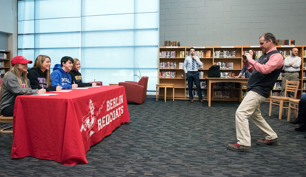 04/05/18 Wesley Bunnell   Staff Berlin Athletic Director Jeff Mauri takes a photo of Berlin High School student athletes who just signed their letters of intent to play college sports. Lexi Kavarsky, L, committed to Sacred Heart, Julia Sisti committed to Stonehill, Noah Silverman to CCSU and Nikki Xiarhos to Bryant.