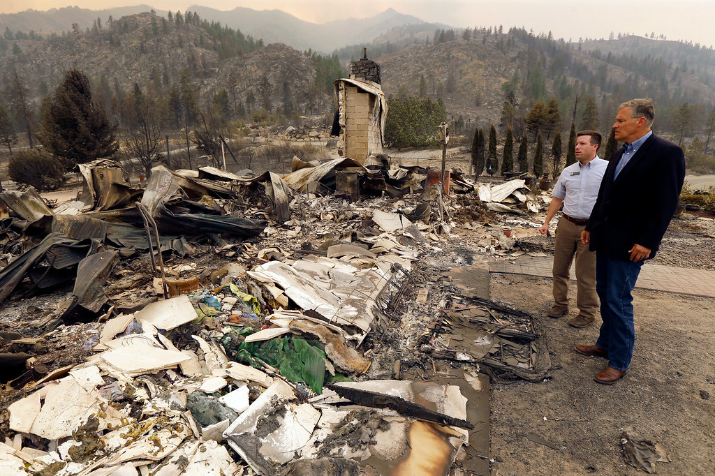 . Washington Gov. Jay Inslee, right, stands with Rep. Brad Hawkins, R-East Wenatchee, second from right, next at the site of a home that was destroyed by wildfires near the Alta Lake Golf Course in Pateros, Wash., Friday, July 18, 2014. The Governor was in the area to access needs and damage after wildfires swept through the region overnight. (AP Photo/Ted S. Warren)