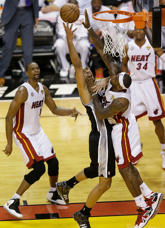 . San Antonio Spurs power forward Tim Duncan (21) and Miami Heat small forward LeBron James (6) collide under the basket during the first half of Game 2 of the NBA Finals basketball game, Sunday, June 9, 2013 in Miami.  (AP Photo/Wilfredo Lee)