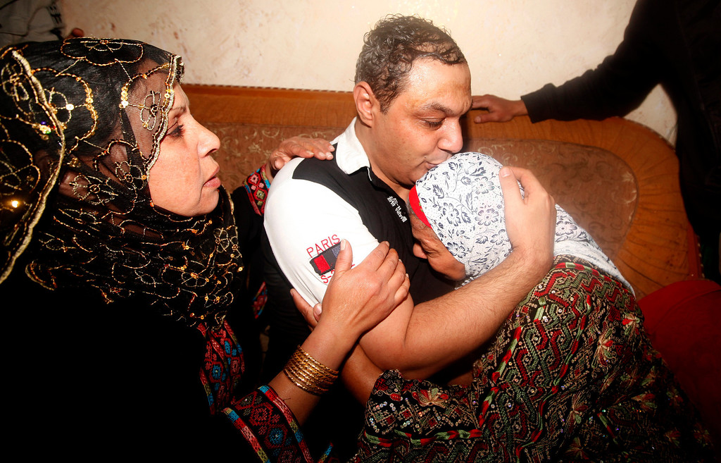 . A released Palestinian prisoner, Ahmed Al Damone, center, is reunited with his mother and sister upon his arrival to his family house in Bureij Refugee Camp, Wednesday, Oct. 30, 2013. Israel freed 26 Palestinian prisoners early Wednesday, the second of four batches to be released as part of a deal that set in motion the current Israeli-Palestinian peace talks. (AP Photo/Hatem Moussa)