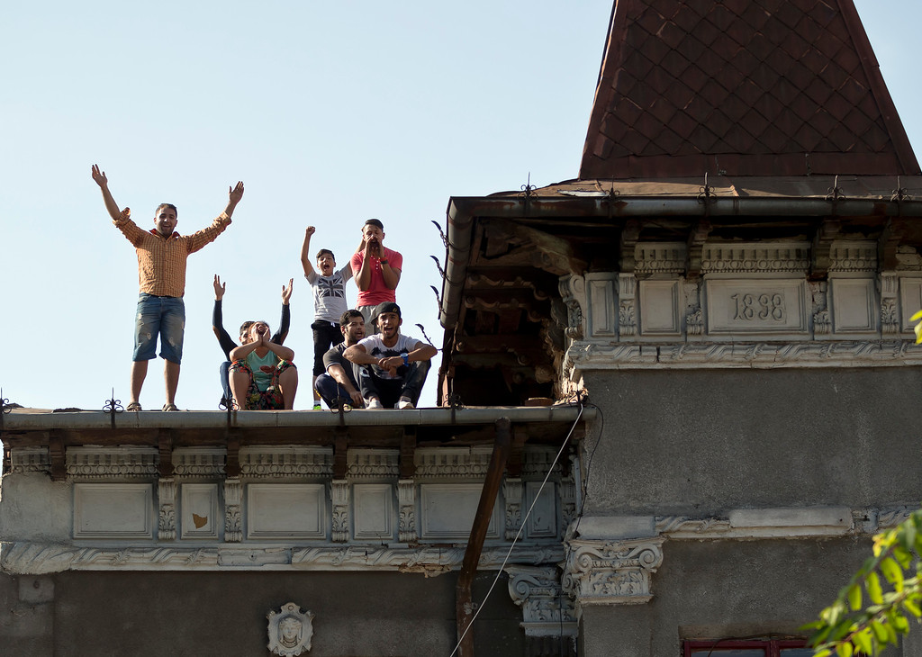. Roma protest standing on a roof whilst more than 100 people are evicted from the homes they lived in, in Bucharest, Romania, Monday, Sept. 15, 2014. (AP Photo/Vadim Ghirda)
