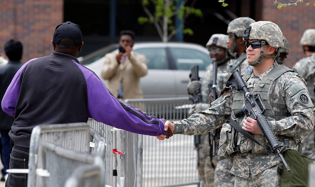 . A man shakes hands with a National Guard soldier outside City Hall, Friday, May 1, 2015 in Baltimore. State\'s Attorney Marilyn J. Mosby announced criminal charges Friday,  against all six officers suspended after Freddie Gray suffered a fatal spinal injury in police custody. Mosby announced the stiffest charge, second-degree depraved heart murder,  against the driver of the police van. Other officers faced charges of involuntary manslaughter, assault and illegal arrest.  (AP Photo/Alex Brandon)